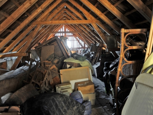 A attic filled with multiple boxes and assorted junk.
