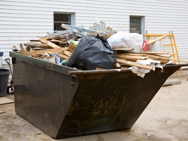A large black dumpster filled with debris left over from home renovations.