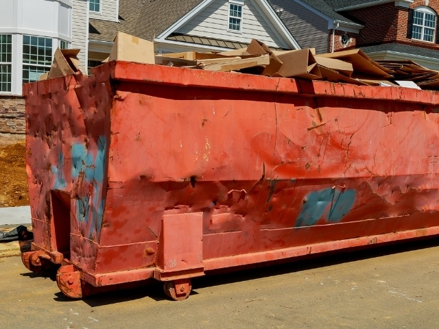 A large red dumpster filled with moving boxes.
